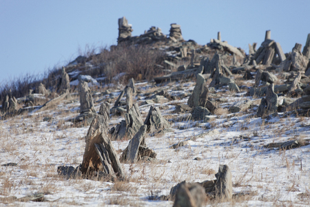 shamanism: Stone pyramids for spirits on Ogoi island. Winter landscape
