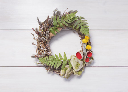 floristry: Wreath with willow twigs, mushrooms and fern on a white wooden background Stock Photo
