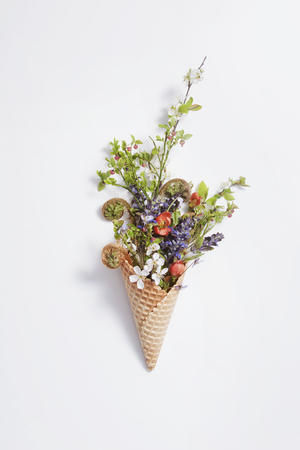 Waffle cone with assorted flowers on white Stock Photo