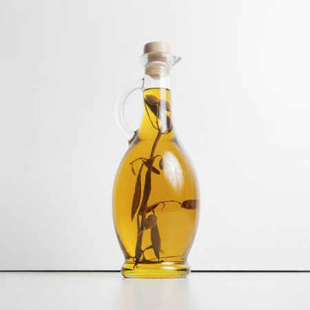 Olive oil in a glass jug with an olive branch inside