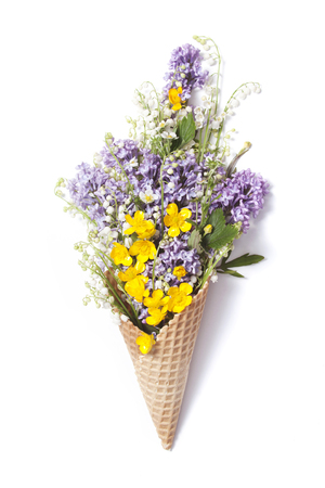 Waffle cone with lily of the valley, buttercup, lilac flowers on white background