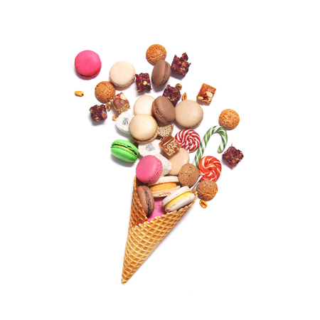 sweettooth: A lot of sweets in a waffle cone on white background