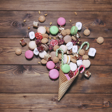 sweettooth: A lot of sweets in a waffle cone on wooden background