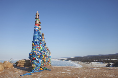 shamanism: Columns with colorful ribbons on Cape Burhan. The sacred place of shamanism. Lake Baikal landscape