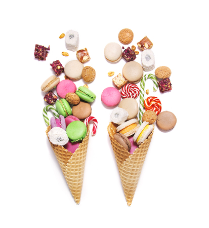 A lot of sweets in a waffle cones on white background