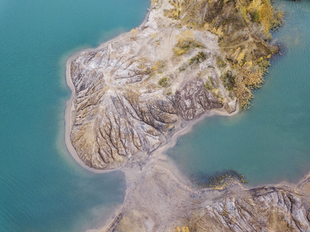 pit fall: Turquoise quarry at Romantsevo (village Konduki). Tula region, Russia. View from above. Autumn landscape