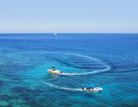Two powerboats floats in a circle. Mediterranean sea