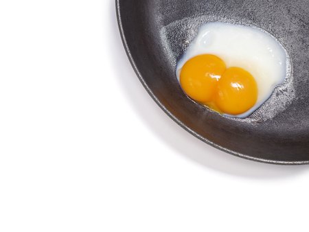 White background with fried egg with two yolks in a frying pan
