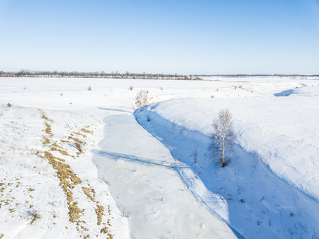 Small frozen river. Ice and snow. Aerial view winter sunny landscape