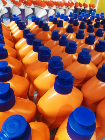 A lot of orange bottles with detergent in the store