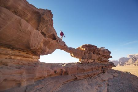 Tourist auf einem Felsen in der Wadi Ram Wüste. Steinbrückenbogen. Jordanien Wahrzeichen