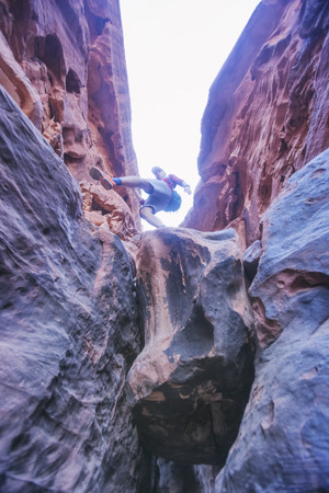 Tourist climbs on the rocks in the canyon of Khazali. Wadi Rum Desert, Jordan