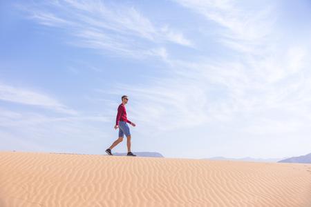 Tourist walks on the sand dune. Wadi Araba desert, Jordan landscape