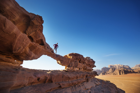 Tourist on a rock in Wadi Ram desert. Stone bridge arch. Jordan landmark Stok Fotoğraf