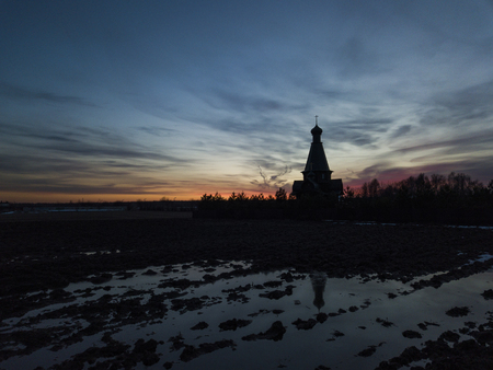 Silhouette of the temple in the name of the Icon of the Mother of God The Bogger of the microdistrict of the Lugovaya town of Lobnya, Moscow region. Sunset landscape