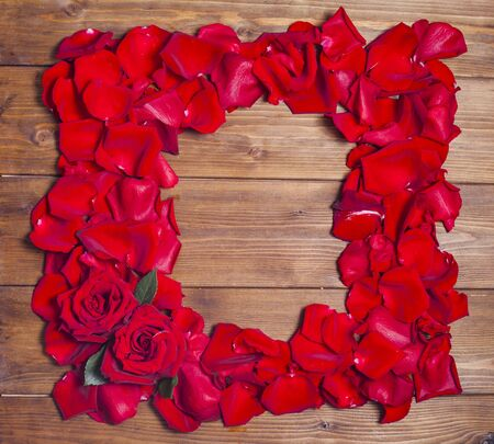 Frame of red roses petals on brown wooden background