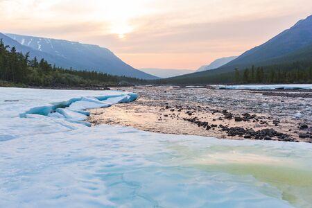 Snow and ice on the banks of the river Khikhikal. Polar day on Putorana Plateau, Taimyr