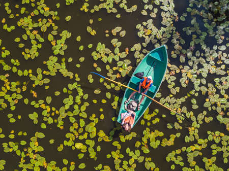 A couple swims on a boat on a pond with water lilies. View from above