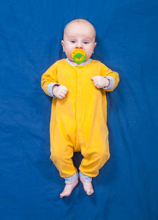 Three month baby boy in a yellow slip with pacifier lies on a blue cloth background 版權商用圖片