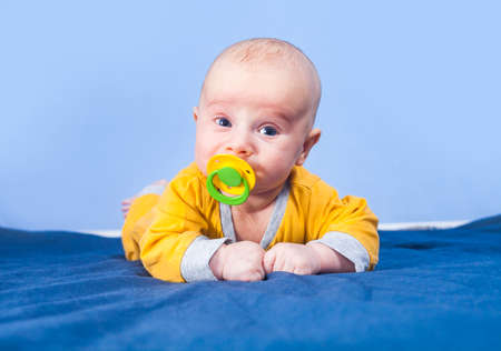 Three month baby boy with pacifier lies on stomach on blue background