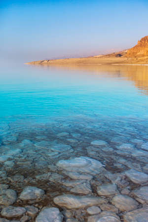 Turquoise water of Dead Sea. Salt at the bottom. Jordan sunset landscape