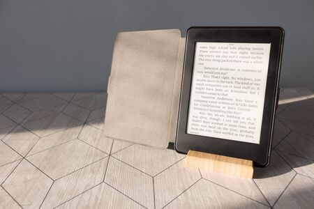 Electronic book on the table under the sunlight, background