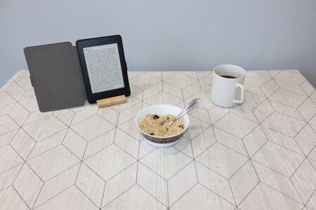 Electronic book and a cup of coffee on the table, background