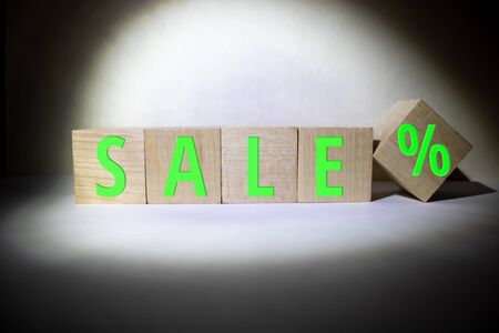 SALE banner concept: word build from wooden cubes with letters, black background, selective focus, free copy space