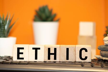 Wooden blocks with the word Ethic. Defending, systematizing and recommending concepts of right and wrong conduct. Moral philosophy Stock Photo