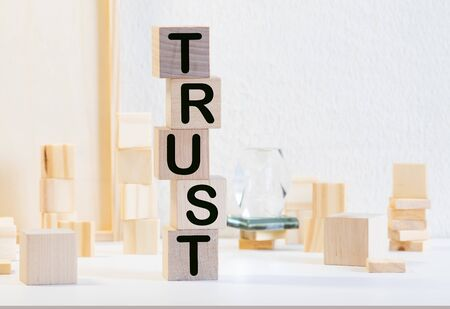 text of TRUST on a wooden background, business concept