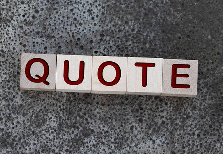 Quotes - word from wooden blocks with letters, citation official notice or quotation concept, grey background Banque d'images