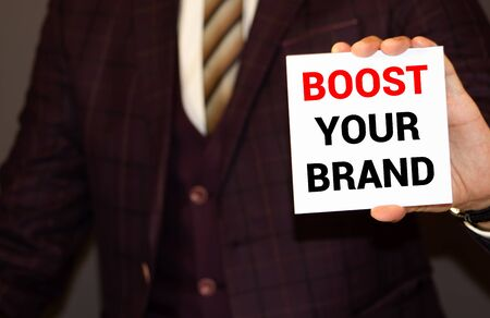 Text sign showing Boost Your Brand. Conceptual photo improve your models name in your field overcome competitors written by Man Notepad holding Marker Wooden background Today Cup and Clip.