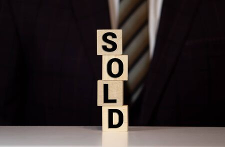 Businessman holding a sold sign composed of stacked wooden blocks balanced on the palm of his hand, conceptual image.