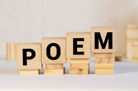 Word poem made with block wooden letters next to a pile of other letters over the wooden board surface composition