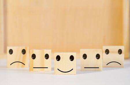 Wooden blocks with the happy face smile face symbol symbol on the table, evaluation, Increase rating, Customer experience, satisfaction and best excellent services rating concept with copy space Imagens