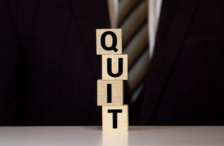 the word quit on wooden cubes on the background of a man in a suit Banque d'images