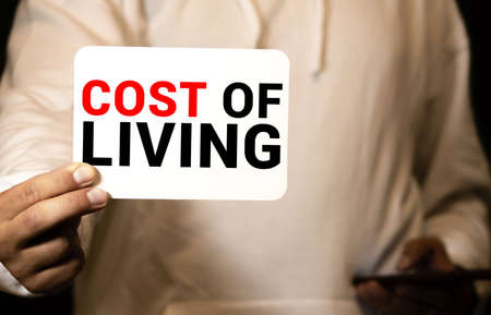 Conceptual hand writing showing Cost Of Living. Business photo text The level of prices relating to a range of everyday items Striped paperboard cardboard office study supplies chart.