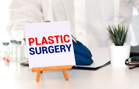 Plastic Surgery Concept written on a card in doctors hands 免版税图像
