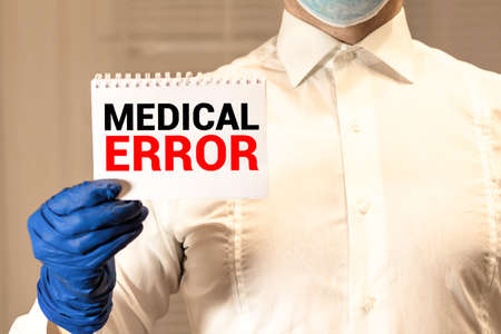 Doctor holding clipboard with medical error text on a sheet of paper on white background