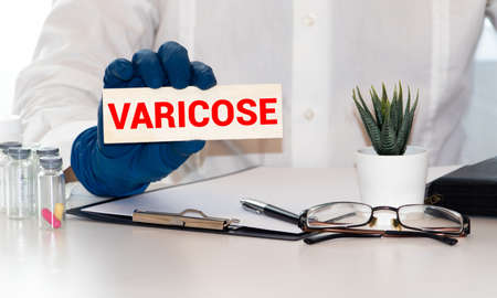 Doctor's hands in blue gloves shows the word varicosity. Medical concept. 版權商用圖片