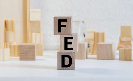 FED, Federal Reserve concept, cube wooden block with alphabet building the word FED at the center on dark blackboard background, the institution to control US financial banking. Archivio Fotografico