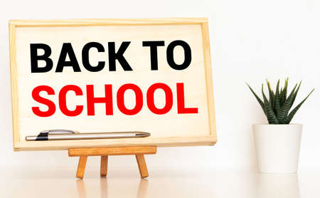wooden plaque with the inscription back to school near stationery on a brown wooden background