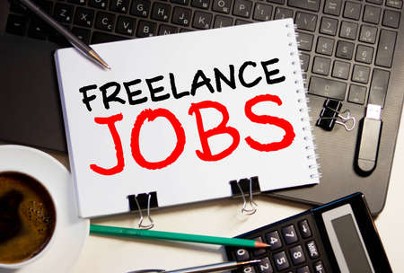 Word writing text FREELANCE JOBS. Business concept for situation in which an employee works mainly from home Note paper taped to black computer screen near keyboard and stationary.