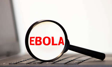 Hand Showing Ebola Through Magnifying Glass On Newspaper Background.