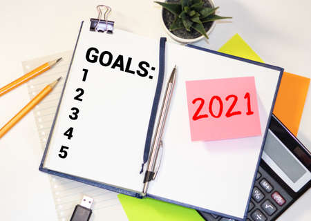GOALS 2021 words written on a white piece of paper laid on a wooden table. Top view, concept in business.