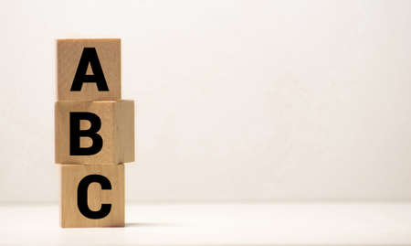 Three toy wooden blocks with letters ABC on them.