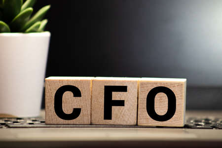 CFO Chief Financial Officer written on a wooden cube in front of a laptop