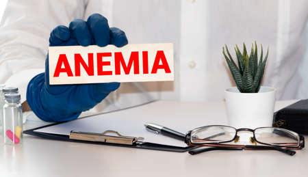 inscription anemia on a piece of paper that holds the hand of a man in a medical glove