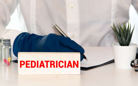 a doctor sitting in a desk with a injured teddy bear and a nameplate with the word pediatrician written in it