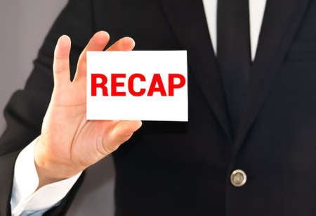 RECAP word on white card paper sheet on in hands of a businessman blurred. recap concept. Stock Photo